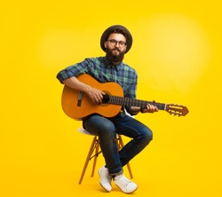 Content hipster man in hat and eyeglasses playing guitar sitting on chair on orange studio background.