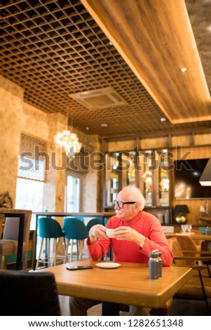 Content introspective senior man in glasses and turtleneck sitting at table and drinking coffee while contemplating in modern restaurant