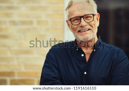 Content senior man with a beard and wearing glasses laughing while standing outside in front of his home #1191616510