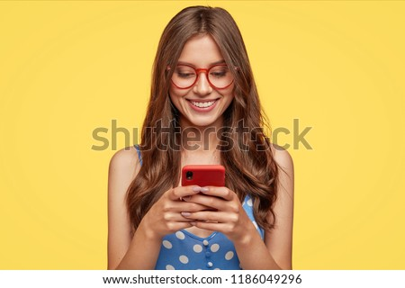 Content teenager with long hair, holds modern cell phone, scrolls through social networks, has cheerful expression, wears spectacles and casual dress, isolated over yellow background, recieves message
