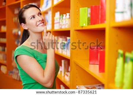 Content woman shopping in pharmacy and looking at shelves