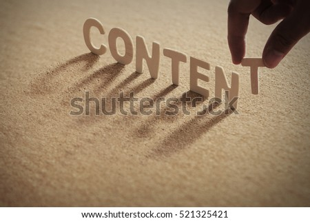 CONTENT wood word on compressed board with human's finger at T letter