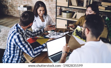 Content young diverse colleagues in casual clothes gathering at table with papers and modern netbook with blank screen during team discussion in contemporary design office Stock photo ©