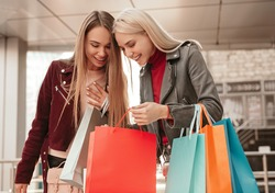 Content young female customer showing purchases in shopping bags to girlfriend and discussing bargain sales after shopping together in modern mall