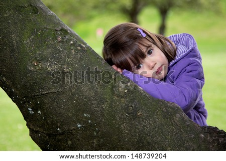 Content young girl deep in thought as she rests on a tree