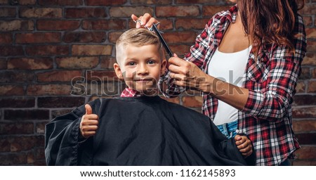 Contented cute preschooler boy shows thumbs up while getting a haircut. Children hairdresser with scissors and comb is cutting little boy in the room with loft interior.