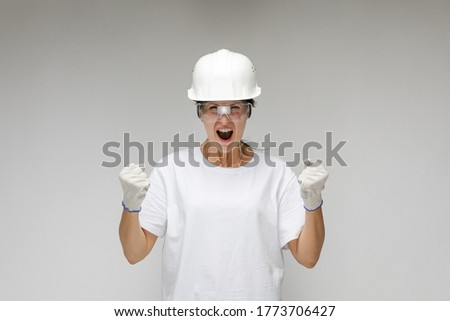 contented girl architect in a construction helmet on a light background