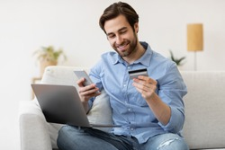 Contented Man Using Cellphone And Credit Card Sitting With Laptop And Shopping Online At Home. Customer Shops With Smartphone. Mobile Banking Application And Payment Verification Concept