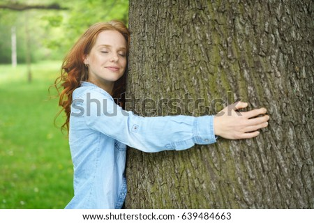 Contented young woman hugging a large tree with a blissful expression and her eyes closed in a concept of nature conservation