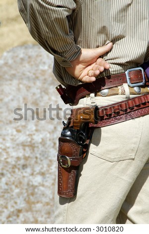 Contestant in period dress wait to compete in a cowboy action shooting event.