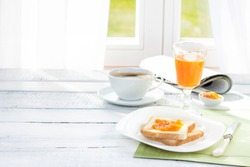 Continental breakfast - coffee, orange juice and toast on white wood table. Background with free text space.