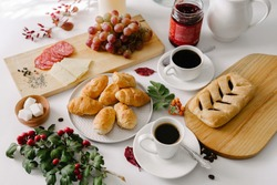 Continental breakfast of mini croissants, pastry, coffee in cups, grapes and jam in a jar, served on white table, decorated with white flowers bouquet