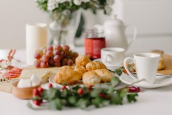 Continental breakfast of mini croissants,pastry,coffee in cups,grapes and jam in a jar,served on white table,decorated with white flowers bouquet,candle and sprig with green leaves and red berries