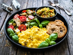 Continental breakfast - scrambled eggs, bread and greek salad on wooden table