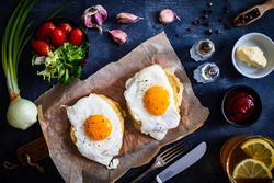 Continental breakfast - sunny side up eggs on baked bun with cheese and vegetable salad on black