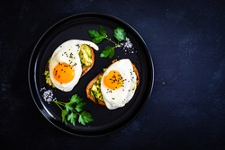 Continental breakfast - sunny side up eggs on toasted bread with avocado on black background