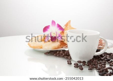 Continental breakfast with assortment of pastries, coffees and flower Orchid in studio shot on coffee beans and white background.