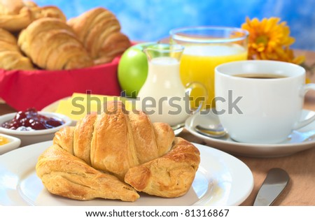 Continental breakfast with croissant, coffee, orange juice, milk, jam, butter and green apple (Selective Focus, Focus on the front of the croissant)