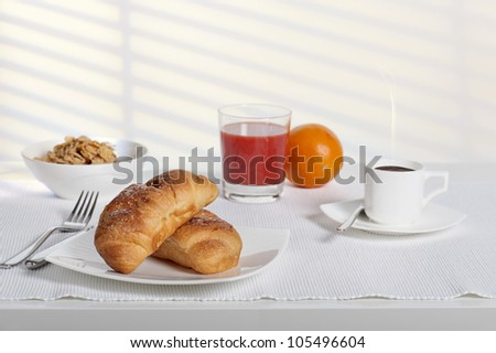 continental breakfast with fresh croissant, coffee, orange juice and corn flakes
