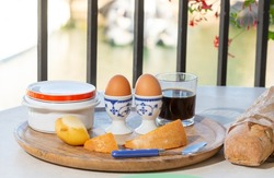 Continental breakfast with soft-boiled chicken egg served outdoor in summer