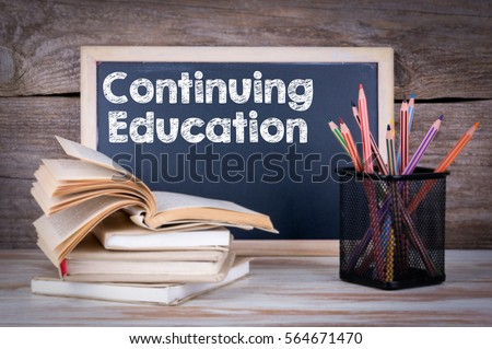 Continuing Education. Stack of books, chalk blackboard with pencils on the wooden table. #564671470