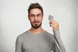 Contraception and healthy lifestyle concept. Male youngster with appealing look, holds condom, has puzzled expression as going to use it firstly. Bearded guy keeps contraceptive, advertises.