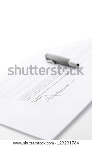 Contract and a pen with copy space. Focus on a signature.