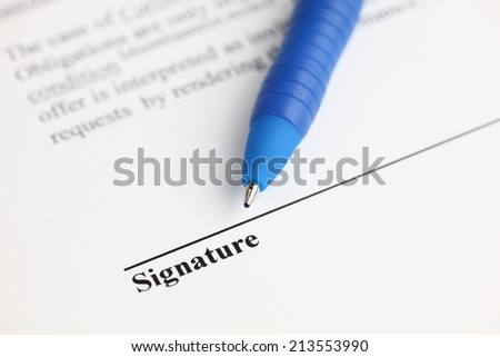 Contract ready for signature. Ballpoint pen on contract. Focus on the end of ballpoint pen. Shallow depth of field. Closeup.