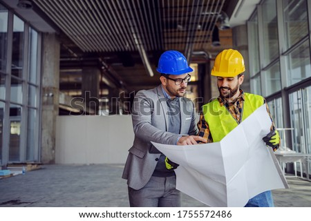 Contractor and architect looking at plan and talking about working on big project. Building in construction process interior.
