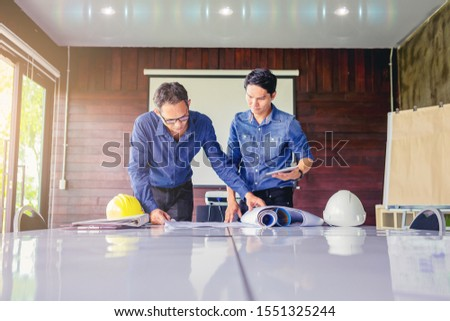 contractor and engineer with blueprints discuss at a modern construction site, Engineers in mechanical factory reading instructions