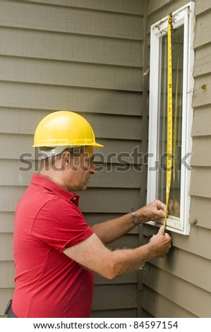 contractor carpenter measuring window for replacement repair