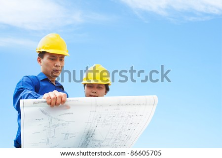Contractor holding blueprint with blue sky background - stock photo