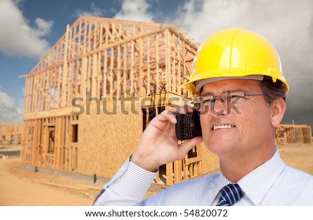 Contractor in Hardhat at Construction Site Talks on His Cell Phone.