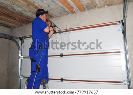 Contractor installing garage door and drilling hole for garage door opener. #779917657