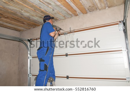 Contractor Installing Garage Door Opener. Garage door springs, garage door replacement, garage door repair.  #552816760