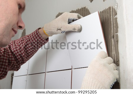 Contractor installing tiles on a wall