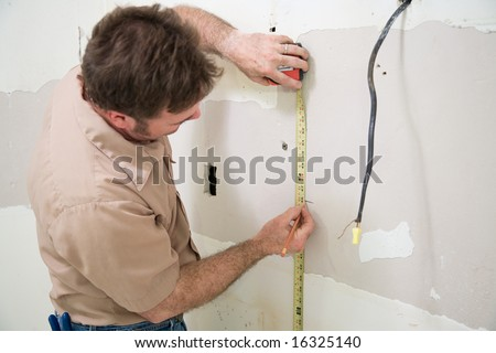 Contractor measuring and marking the drywall where he wants to cut out an opening for an electrical box.  Authentic and accurate content depiction.