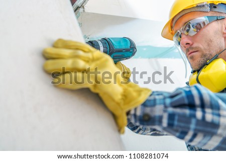 Contractor Remodeling Job. Caucasian Worker with Cordless Driller Installing Drywall Elements. Hard Hat Construction Zone