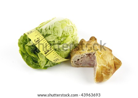Contradiction between healthy food and junk food using a green salad lettace and pork pie with a yellow tape measure on a reflective white background