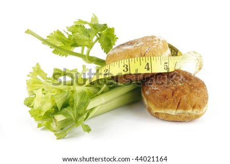Contradiction between healthy food and junk food using celery and jam doughnut with a yellow tape measure on a reflective white background