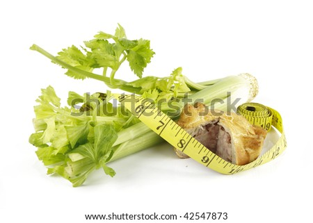 Contradiction between healthy food and junk food using celery and pork pie with a tape measure on a reflective white background