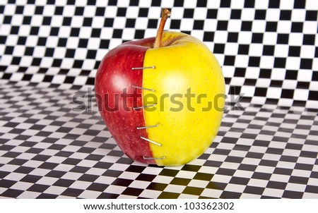 Contrast apple with two different halves on a black and white check paper