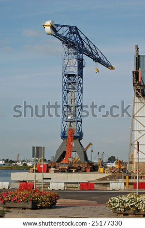 contrast between shipyard crane on the quay in the harbor with colorful flower containers in the front