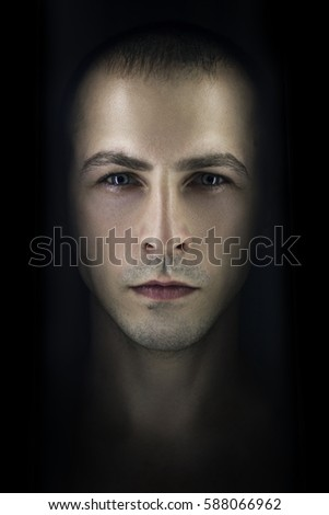 Contrasting male portrait on black background. Light and shadow on the man's face. Stylish, brutal man, art photo. Silhouette face serious macho, expressive eyes