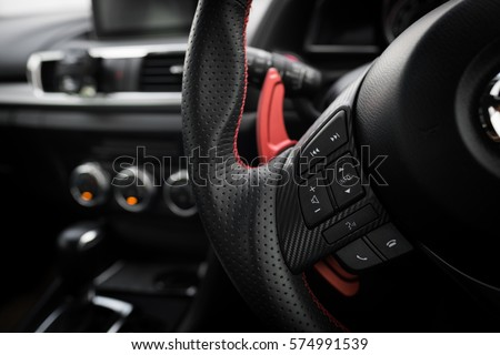 Control buttons on steering wheel in a modern car. #574991539