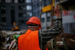 Control construction process. Builder are working with orange color of safety helmet and safety vest on grey wall background. An elderly construction worker in an orange vest and red helmet.