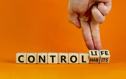 Control habits symbol. Businessman hand turns wooden cubes and changes words 'control habits' to 'control life'. Beautiful orange background, copy space. Business and control habits concept.