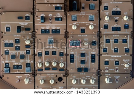 control panel knobs and buttons in a big jet plane cockpit #1433231390