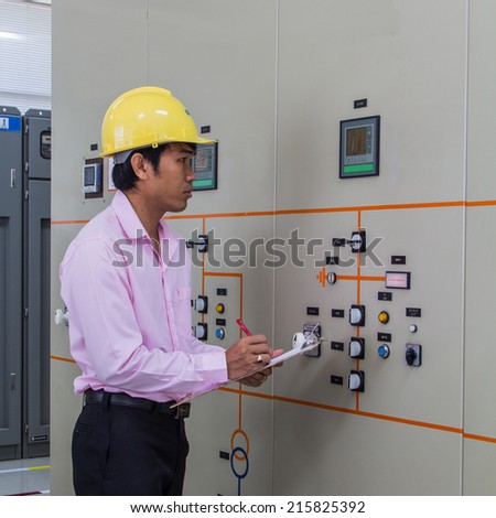 Control Room Engineer. Power plant control panel. Engineer standing in front of the control panel in the control room and writes the results of measurements.