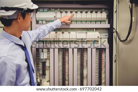 Control Room Engineer. Power Plant Control Panel. Engineer standing in front of the control panel in the control room and write the results of the measurements. #697702042